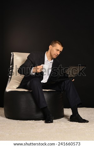 Happy Businessman on black background with laptop - stock photo
