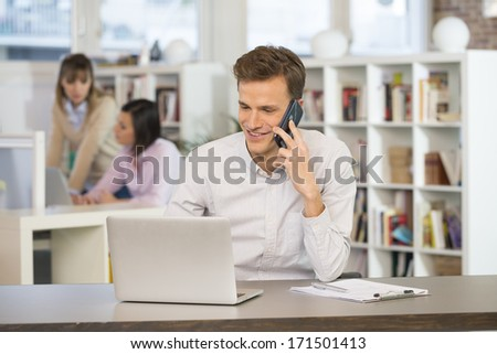 Happy Businessman on phone in office - stock photo