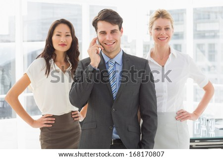 Happy businessman on the phone in front of his team in the office - stock photo