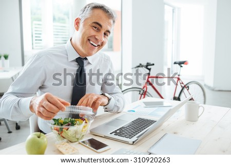 Happy businessman opening his salad pack and having a lunch break at office desk - stock photo