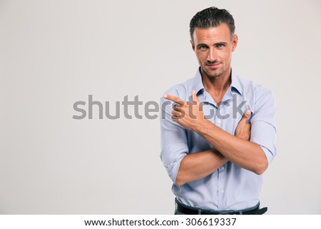 Happy businessman pointing finger away over gray background. Looking at camera - stock photo