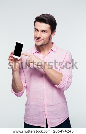 Happy businessman pointing finger on smartphone screen over gray background. Looking at camera - stock photo