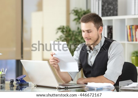 Happy businessman reading a letter sitting in a desk at office - stock photo