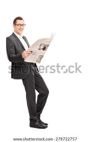 Happy businessman reading a newspaper and leaning against a wall isolated on white. The newspaper is custom made, language Latin, pictures my copyright.  - stock photo