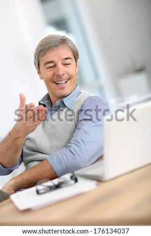 Happy businessman reading good news on laptop - stock photo