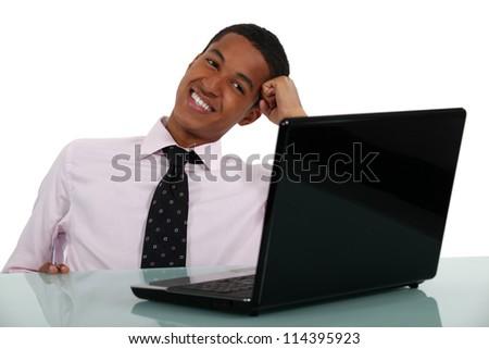 Happy businessman sat at his desk - stock photo