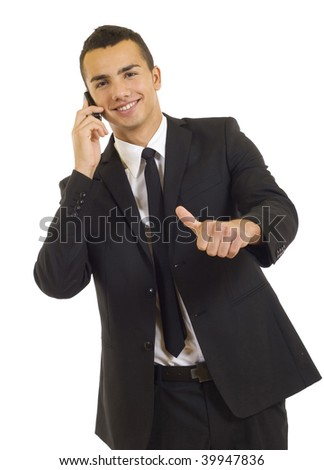 Happy businessman showing thumb up while talking on the phone - stock photo
