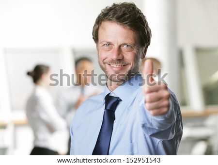 Happy businessman showing thumbs up sign - stock photo