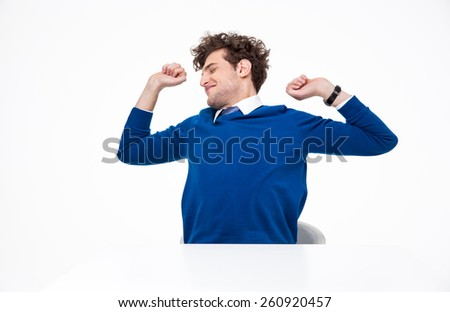 Happy businessman sitting at the table and stretching - stock photo