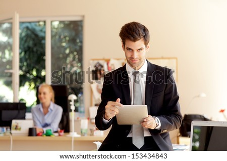 Happy businessman sitting on desk and holding a digital tablet in his office. Shallow Focus. - stock photo