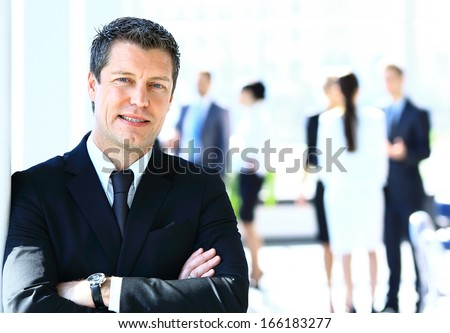 Happy businessman standing in front of his colleagues in office - stock photo
