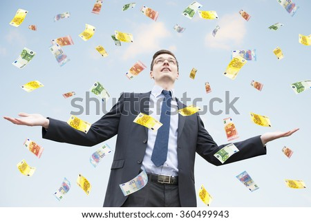 Happy businessman standing in the rain of euro money.  Euro are falling from the sky - stock photo