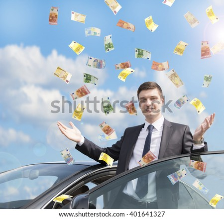 Happy businessman standing near his car in the rain of euro money.  Euro are falling from the sky - stock photo