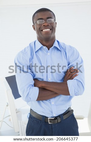 Happy businessman standing with arms crossed in his office - stock photo