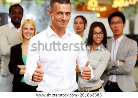 Happy businessman standing with thumbs up in front his colleagues - stock photo