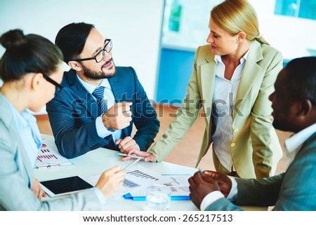 Happy businessman talking to pretty employee at meeting with colleagues near by - stock photo