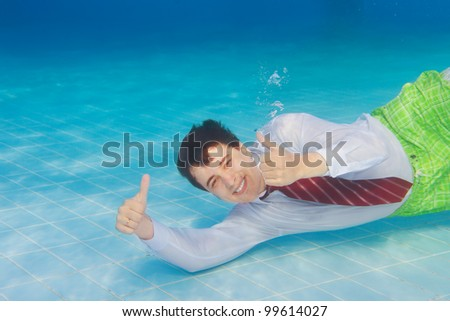 Happy businessman underwater with thumbs up swimming underwater in the pool - stock photo