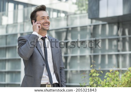 Happy businessman using cell phone outside office - stock photo