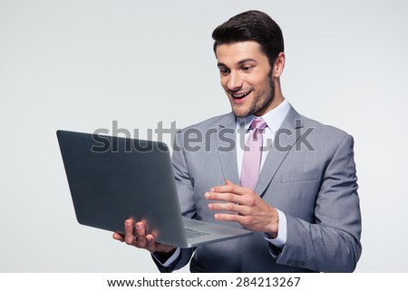 Happy businessman using laptop over gray background - stock photo