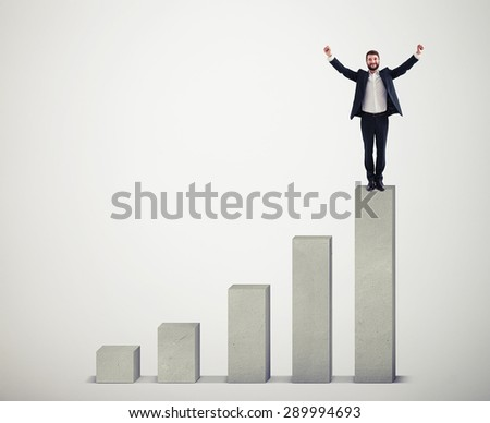 happy businessman winner standing on top of concrete diagram over light grey diagram - stock photo