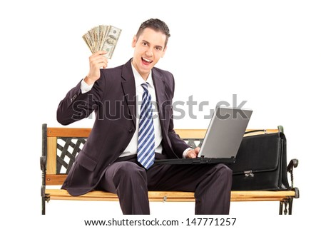 Happy businessman with laptop sitting on a wooden bench and holding US dollars isolated on white background - stock photo