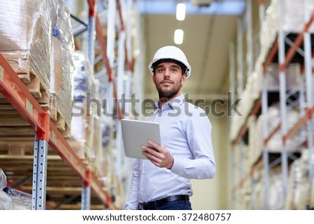 happy businessman with tablet pc at warehouse - stock photo