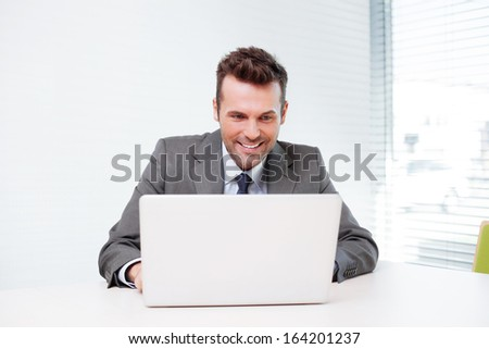 Happy businessman working on laptop in the office - stock photo