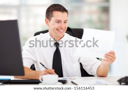 happy businessman writing report in his office - stock photo