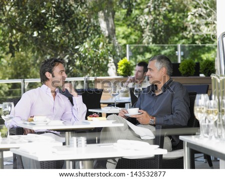 Happy businessmen conversing at outdoor cafe - stock photo