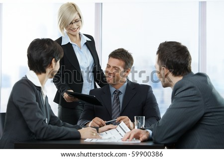 Happy businesspeople at meeting in office, standing assistant handing over contract to executive sitting with colleagues.? - stock photo