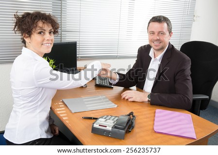 Happy Businesspeople In Office Shaking Hands - stock photo