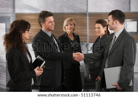 Happy businesspeople shaking hands greeting each other before business meeting in office. - stock photo