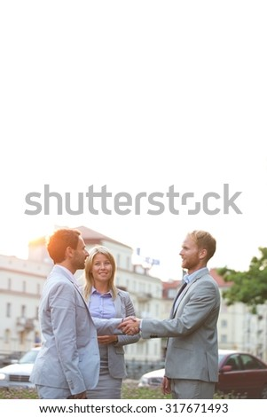 Happy businesspeople shaking hands in city against clear sky - stock photo