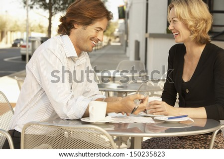 Happy businesspeople with documents sitting at outdoor cafe - stock photo