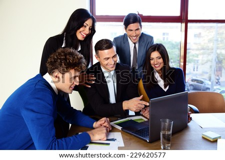 Happy businesspeople working in the office together - stock photo