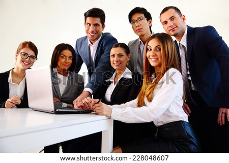 Happy businesspeople working on the laptop together - stock photo