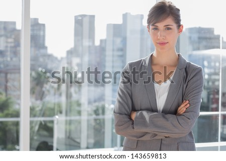 Happy businesswoman beside large window with arms crossed - stock photo