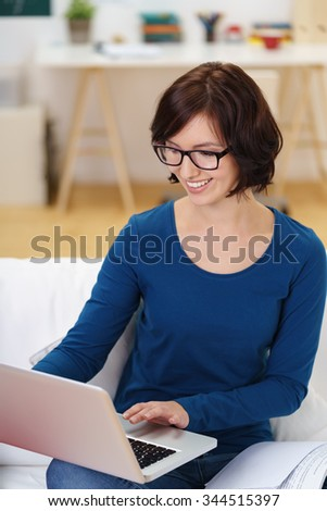 Happy Businesswoman Busy Working on her Laptop Computer at the Couch Inside the Office. - stock photo