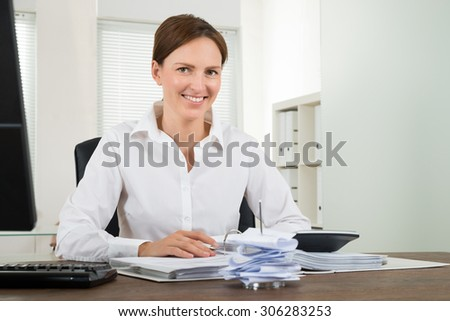 Happy Businesswoman Calculating Bills With Calculator At Desk - stock photo