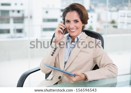 Happy businesswoman calling with smartphone in bright office - stock photo