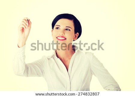 Happy businesswoman drawing on a glassboard - stock photo