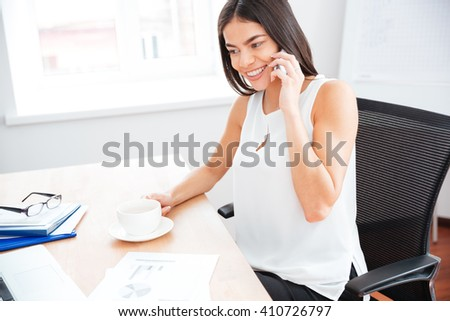 Happy businesswoman drinking coffee and talking on the phone in office - stock photo