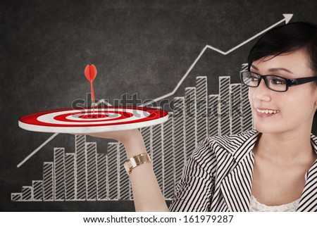 Happy businesswoman holding up a target on her hand - stock photo
