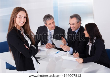Happy Businesswoman In Front Of Her Colleagues - stock photo
