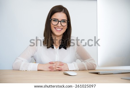 Happy businesswoman in glasses sitting at the table in office - stock photo
