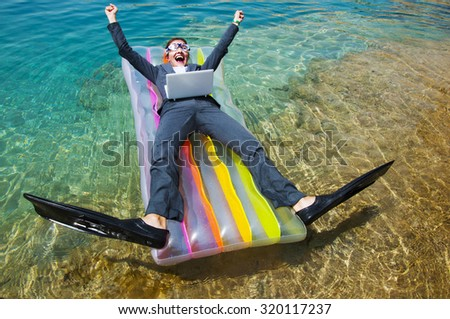 Happy businesswoman in goggles and flippers with laptop on floating mattress. Travel concept  - stock photo