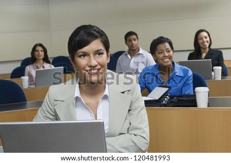 Happy businesswoman in presentation with business colleagues sitting in the background - stock photo