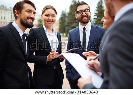 Happy businesswoman looking at camera among busy colleagues - stock photo