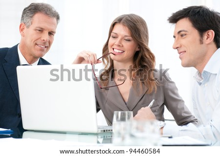 Happy businesswoman looking at coputer with her business colleagues at office - stock photo