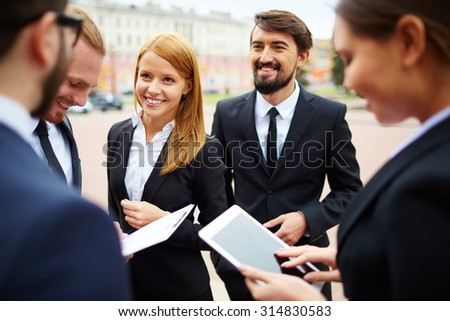 Happy businesswoman looking at her colleague during conversation - stock photo